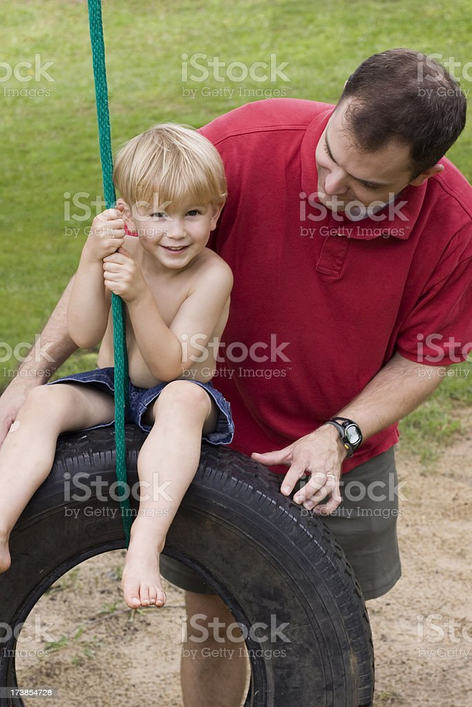Father son spending time together on tire swing royalty-free stock photo