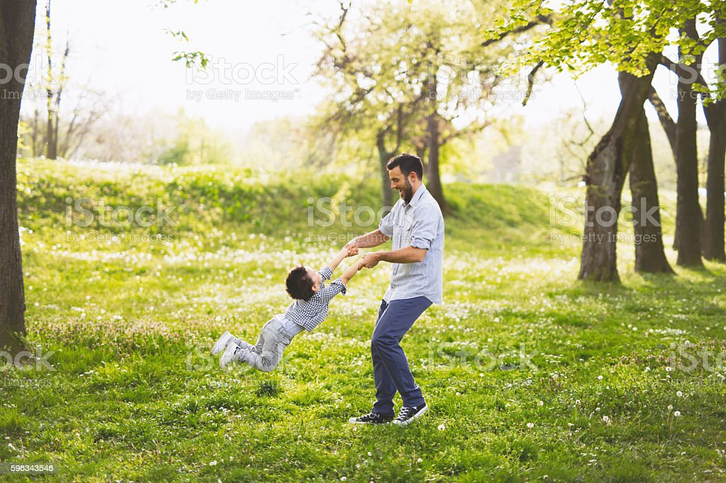 Father spinning his son in the park Lizenzfreies stock-foto