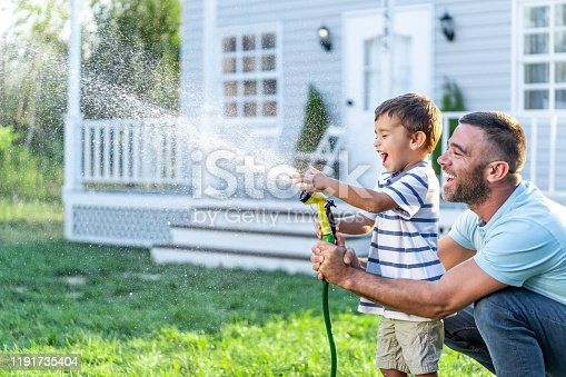 Father splashing water and having fun with son on back yard