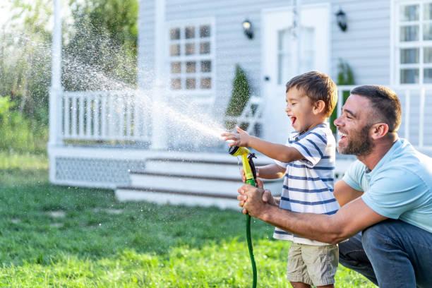 Vater spritzt Wasser und Spaß mit Sohn auf Hinterhof – Foto