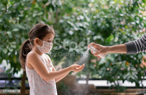 Father squirts antibacterial hand sanitizer in daughter's hands, Little girl wears a face mask during coronavirus and flu outbreak