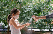 istock Father squirts antibacterial hand sanitizer in daughter's hands, Little girl wears a face mask during coronavirus and flu outbreak 1214546778