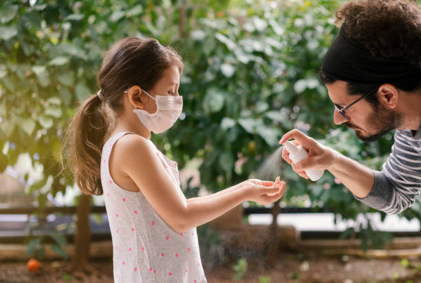 Father squirts antibacterial hand sanitizer in daughter's hands, Little girl wears a face mask during coronavirus and flu outbreak stock photo