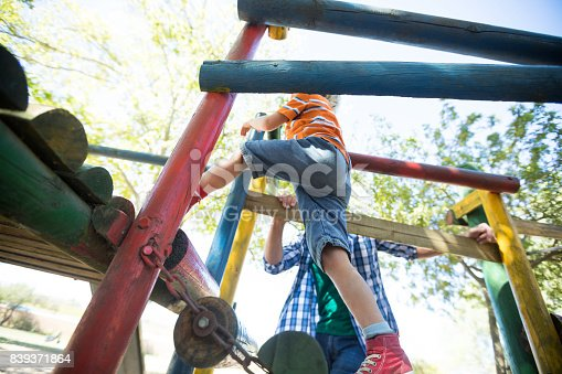 istock Father standing by boy moving up on outdoor play equipment 839371864