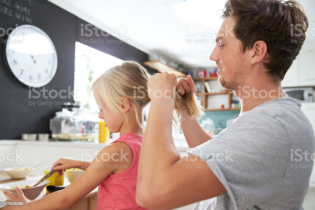 父と娘のヘアスタイリングでの朝食用テーブル ストックフォト