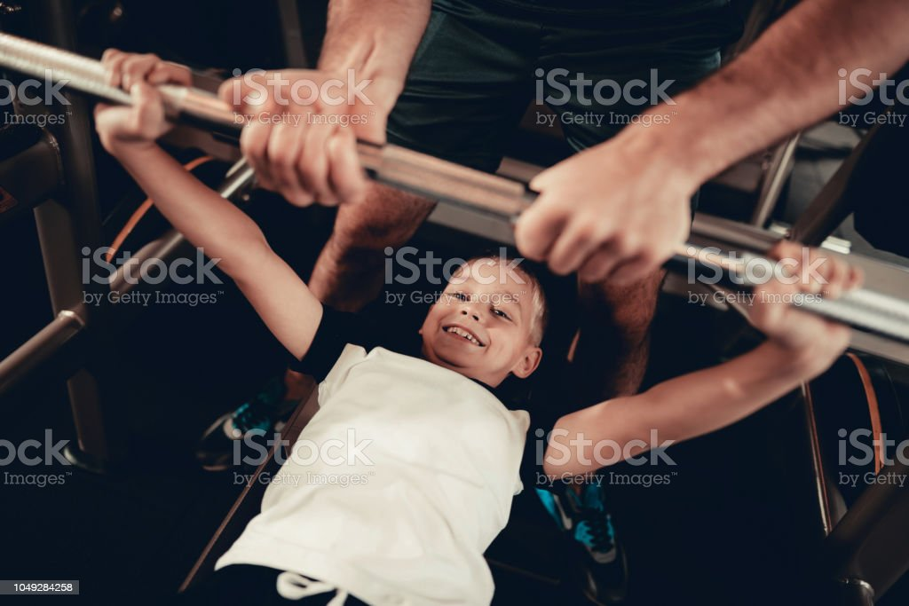 Father Support To Son While Lifting The Barbell. stock photo