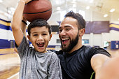 The mid adult father laughs and takes a selfie while his son holds a basketball on his head.