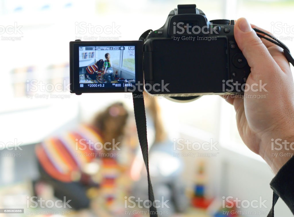 Father Taking a Photo While Children is Playing stock photo