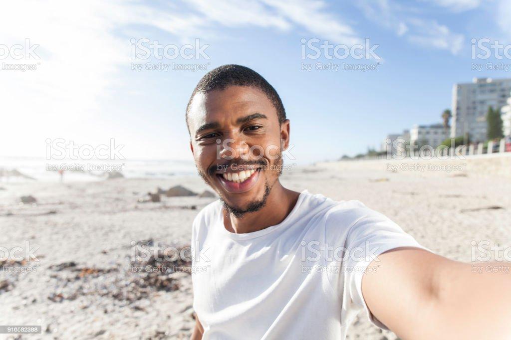 Père de prendre un selfie de lui-même sur la plage. - Photo