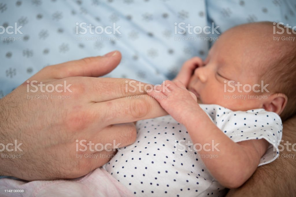 Father taking care of his premature baby at hospital. Color and...