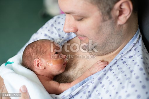 Father taking care of his premature baby  doing skin to skin at hospital. Color and horizontal photo was taken in Quebec Canada.