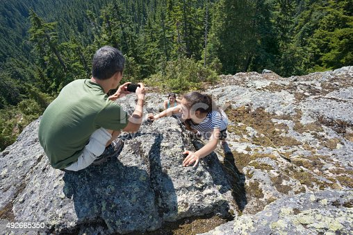 903015102 istock photo Father Taking Photo with Cellphone of Girl Hikers Rock Climbing 492665350