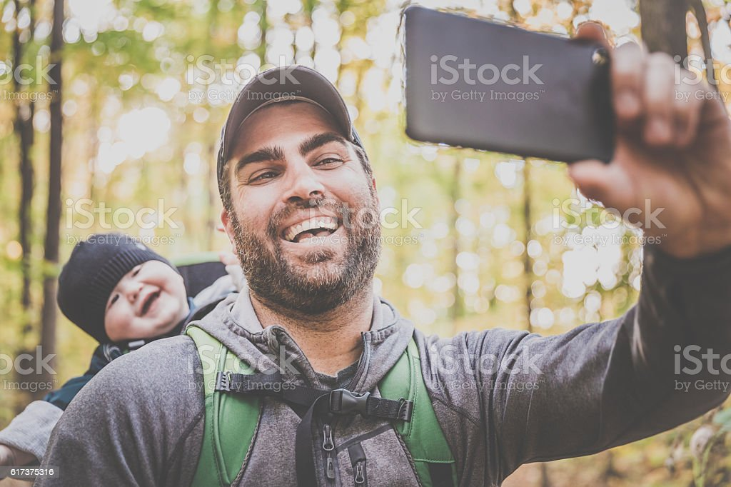 Father Taking Selfie with Baby in Forest stock photo