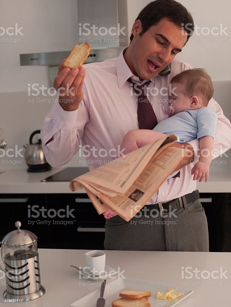 Father talking on phone with toast while holding baby daughter in a kitchen stock photo
