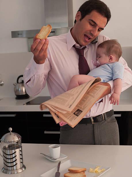 vater spricht am telefon mit toast und hält baby - porzellan druck stock-fotos und bilder