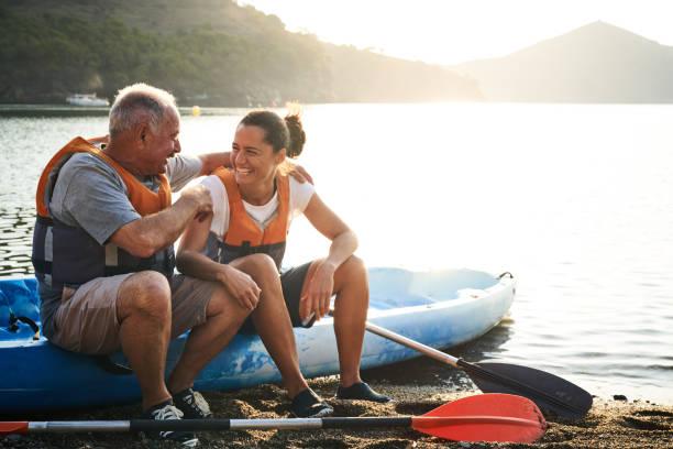 Father talking to daughter while sitting on kayak stock photo