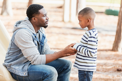 An African-American man in his 30s with a serious expression on his face, talking to his 7 year old son on a playground. They are face to face, and he is holding his hands. The boy may have been naughty and is being disciplined.