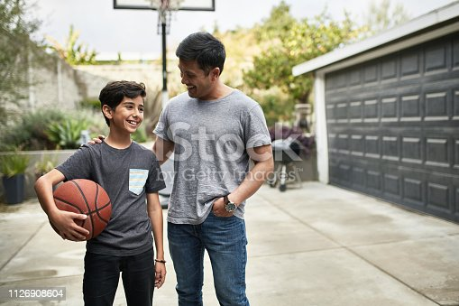 Father talking to smiling son with basketball. Happy mid adult man and child are standing in backyard. They are wearing casuals.
