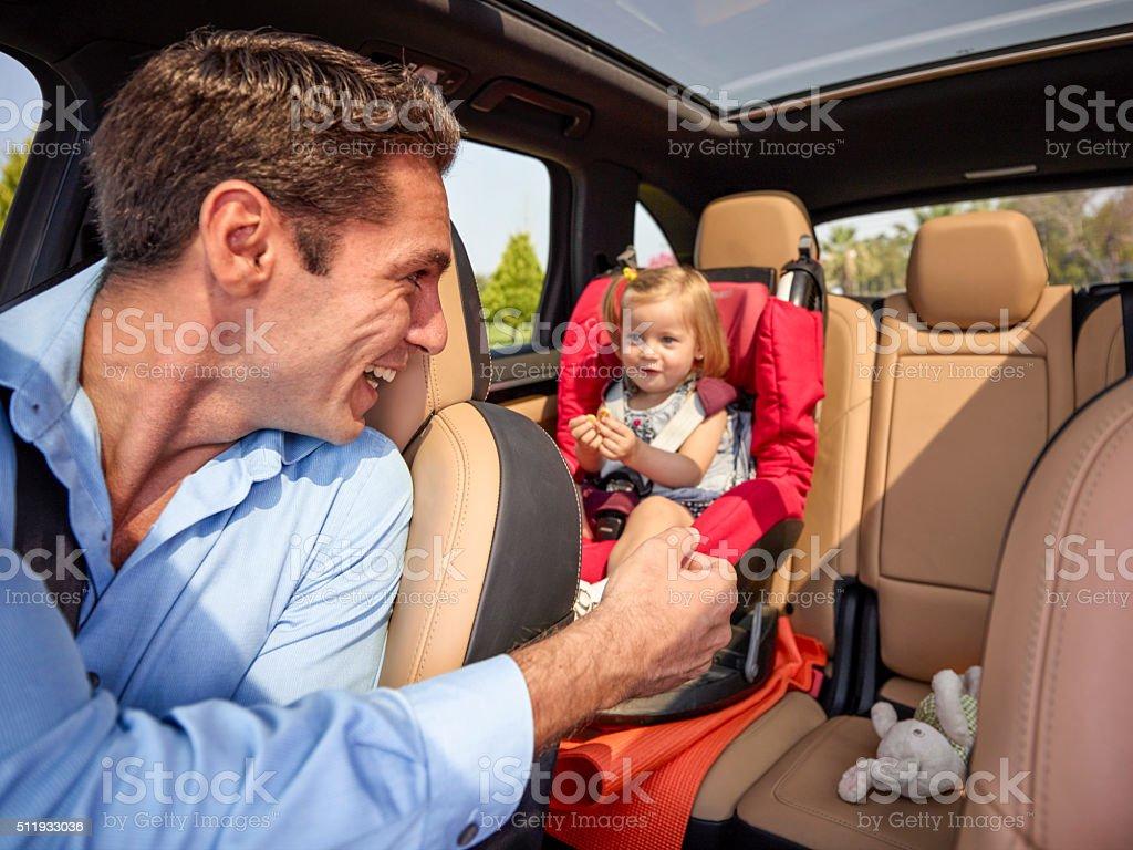 Père parler avec sa fille dans un siège de voiture - Photo