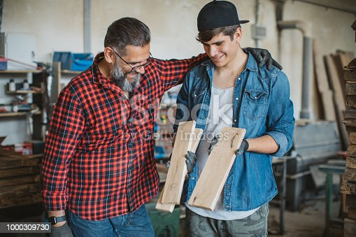 1000309654istockphoto Father teach son to be good carpenter 1000309730