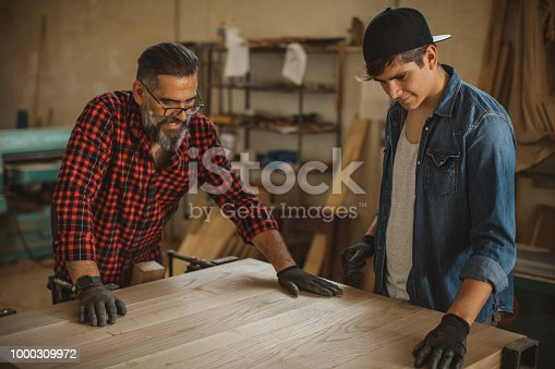 1000309654istockphoto Father teach son to be good carpenter 1000309972