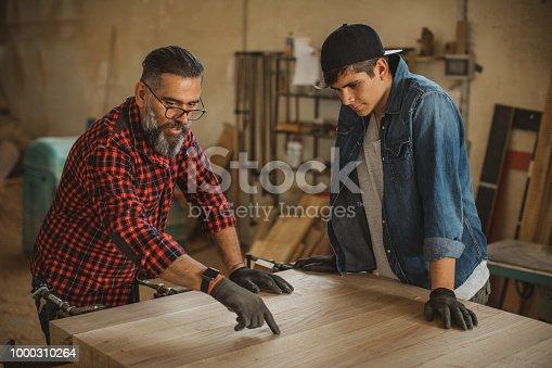 1000309654 istock photo Father teach son to be good carpenter 1000310264