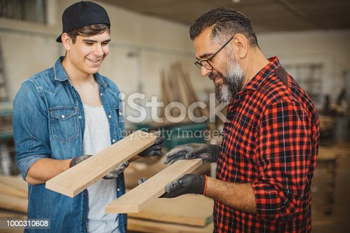 1000309654istockphoto Father teach son to be good carpenter 1000310608