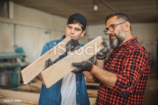 1000309654 istock photo Father teach son to be good carpenter 1000314994