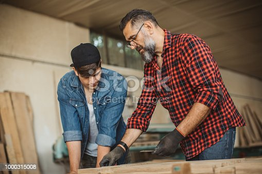 1000309654istockphoto Father teach son to be good carpenter 1000315008