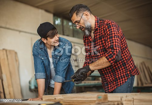 1000309654istockphoto Father teach son to be good carpenter 1000315010