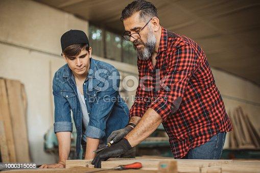 1000309654 istock photo Father teach son to be good carpenter 1000315058