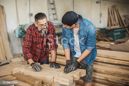 1000309654istockphoto Father teach son to be good carpenter 1019842304