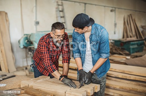 1000309654istockphoto Father teach son to be good carpenter 1019842318
