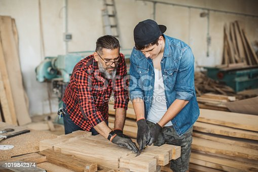 1000309654istockphoto Father teach son to be good carpenter 1019842374
