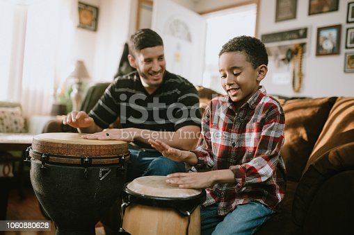 A dad plays djembe drum with his son in their living room, teaching the boy technique on how to play the instrument.