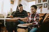 Father Teaches Child To Play Hand Drum