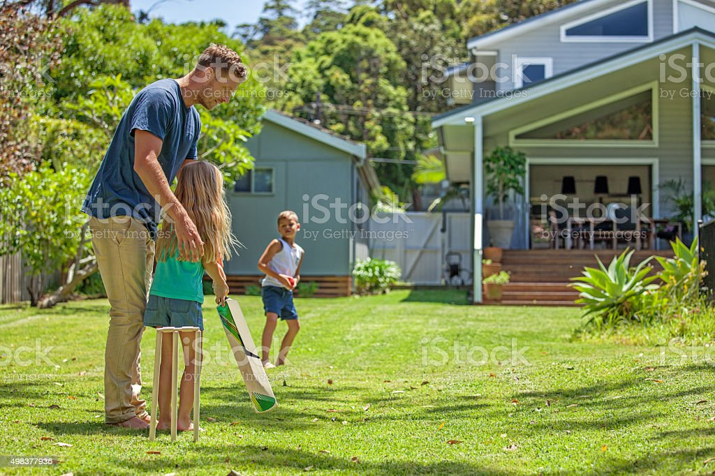 father teaches daughter cricket stock photo