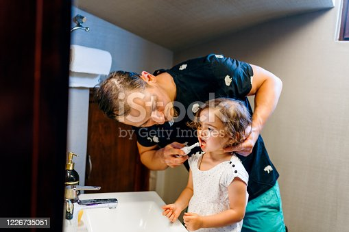 684029036 istock photo father teaches his daughter how to brush teeth 1226735051