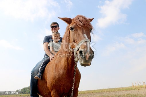 istock father teaches his son to ride on red horse 619065794