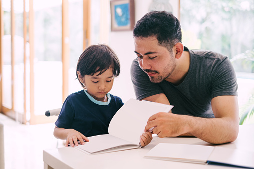 Father Teaches His Son with Books