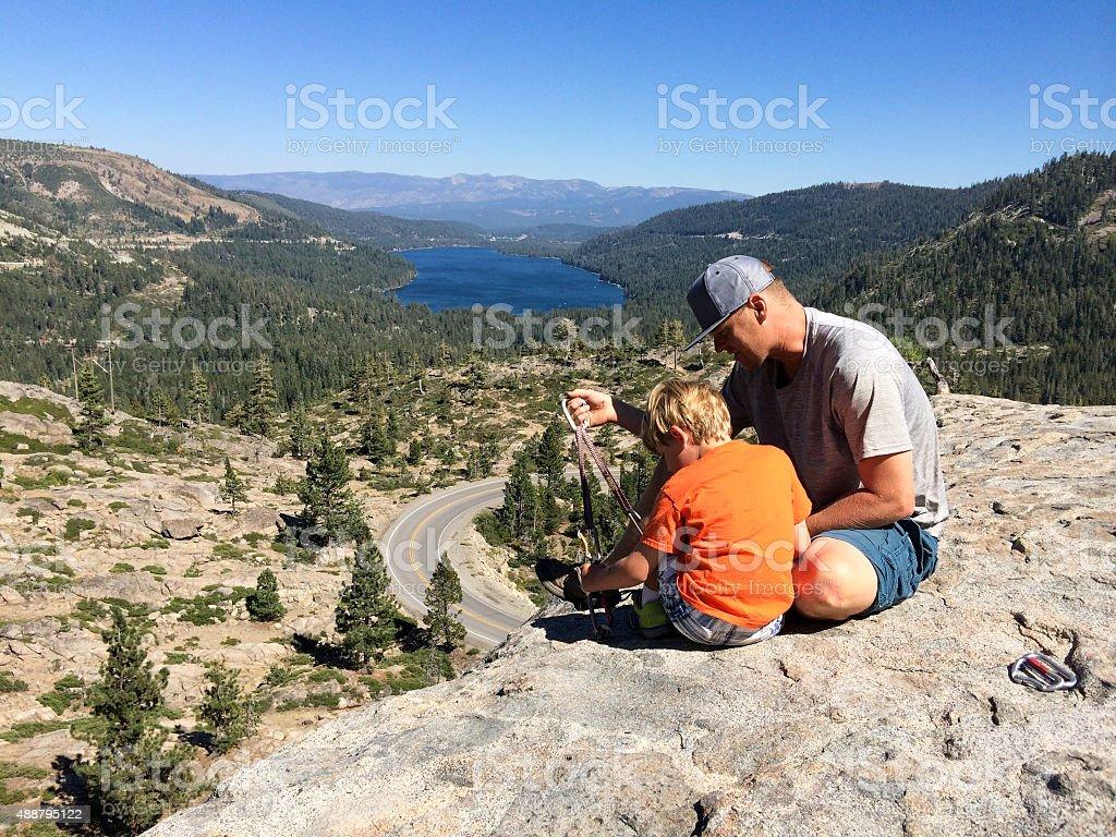 Father teaches son about climbing stock photo