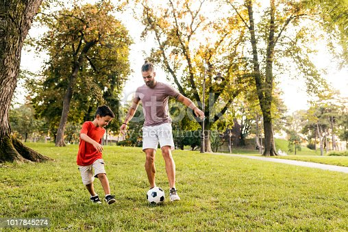 Photo of hipster Handsome young dad with his little cute sun are having fun and playing football on green grassy lawn. Father and 5 years old son playing football in park at sunny day