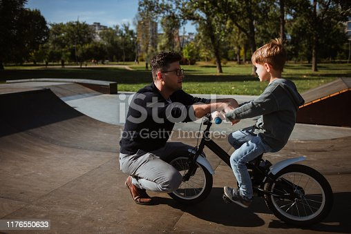 860036242 istock photo Father teaches son the basics of driving bicycle 1176550633