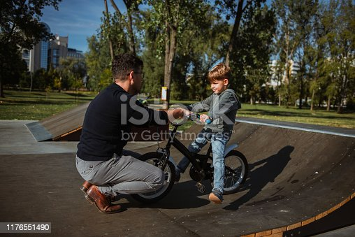 860036242 istock photo Father teaches son the basics of driving bicycle 1176551490