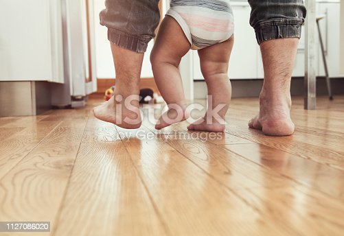 First steps of a child with his father's help. Both barefoot on hardwood floor. What a joy.....