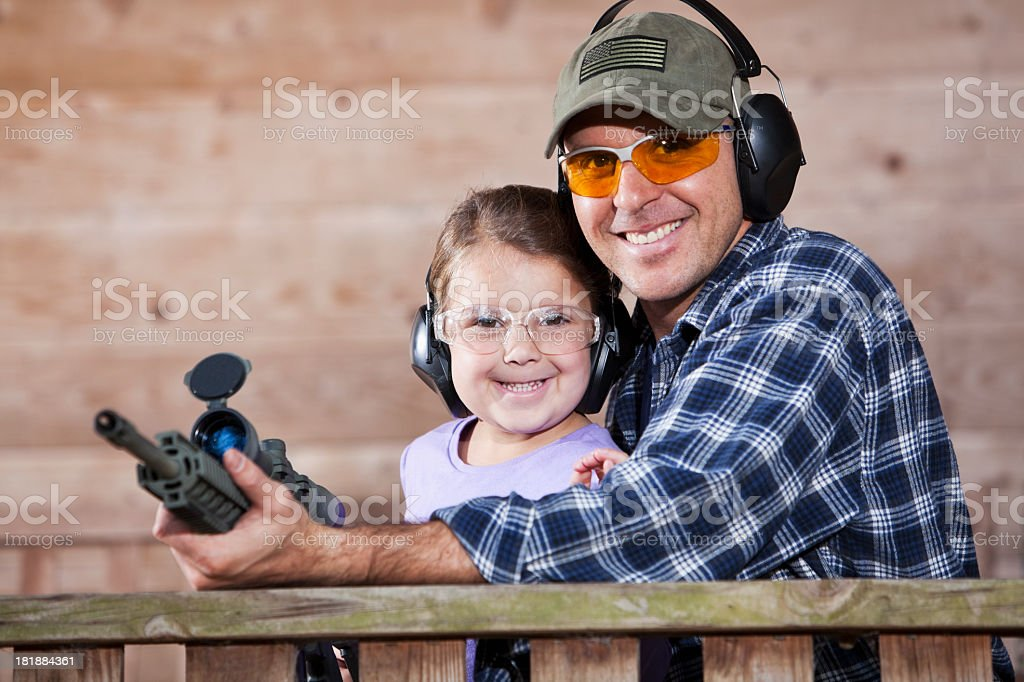 Father teaching child to handle gun royalty-free stock photo