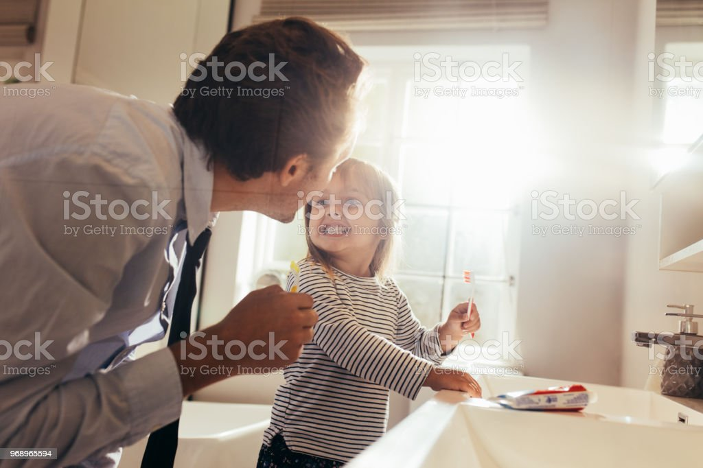 Father teaching daughter how to brush teeth stock photo