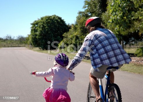 istock Father teaching daughter how to ride a bike 172288927