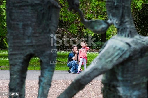 Dublin, Ireland - June 2, 2013: In Dublin's St. Stephen's Green, a father kneels beside his young daughter and points to a sculpture commemorating the Irish famine, explaining it to her. The sculpture is the work of Edward Delaney.