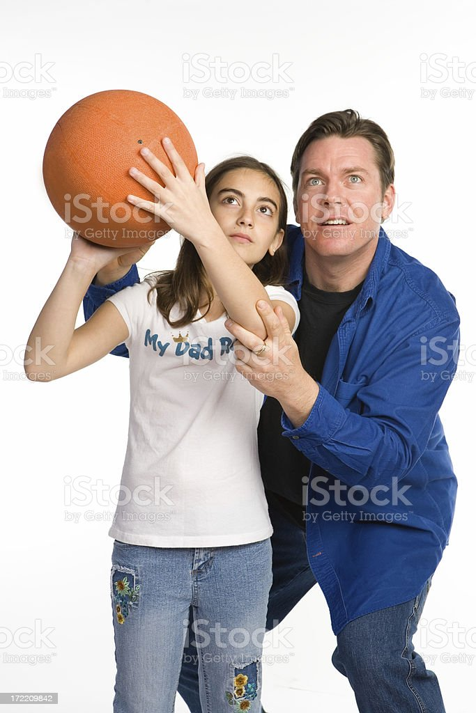 Father teaching daughter to play basketball royalty-free stock photo